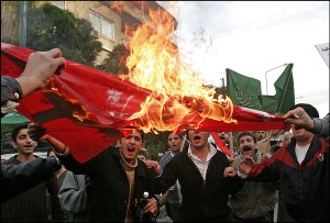 Syrians burn the Danish flag to protest against the printing of cartoons depicting Prophet Mohammad by a Danish newspaper in Damascus